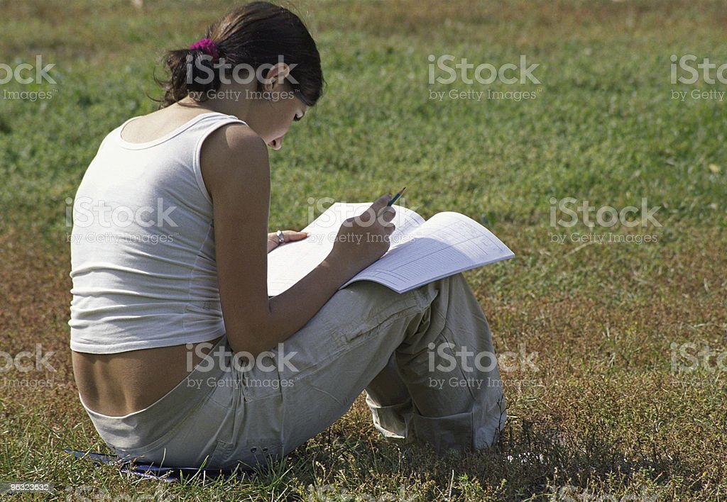 Student girl reading notebook on grass royalty-free stock photo