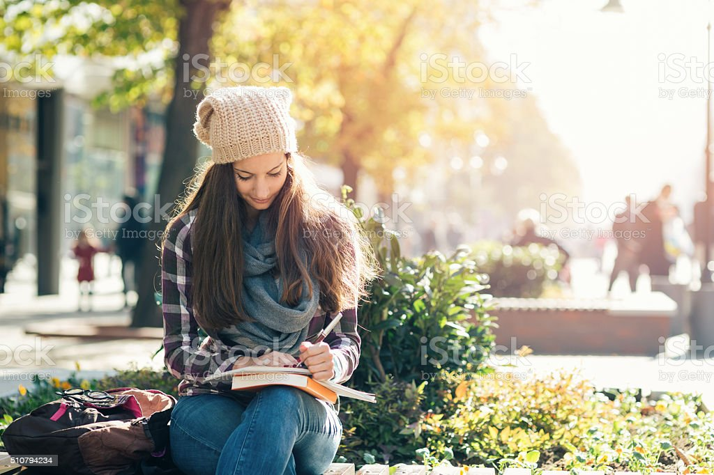 Student girl writing in notebook and studying. Casual clothing, scarf...