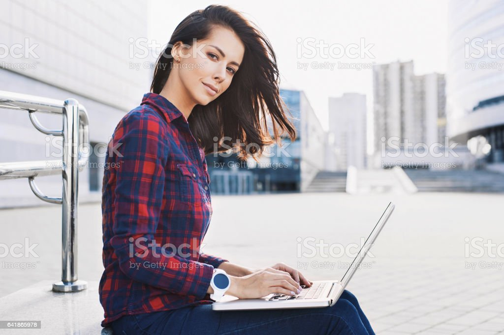Student girl using laptop outdoors stock photo