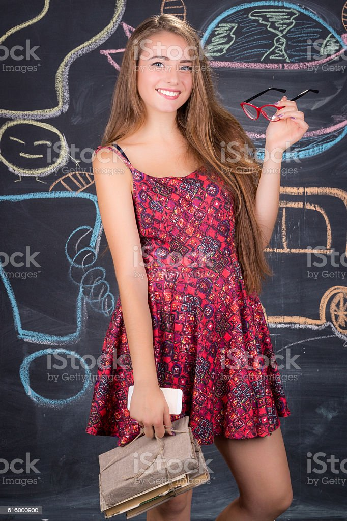 Student girl with books poses in front of class blackboard stock photo