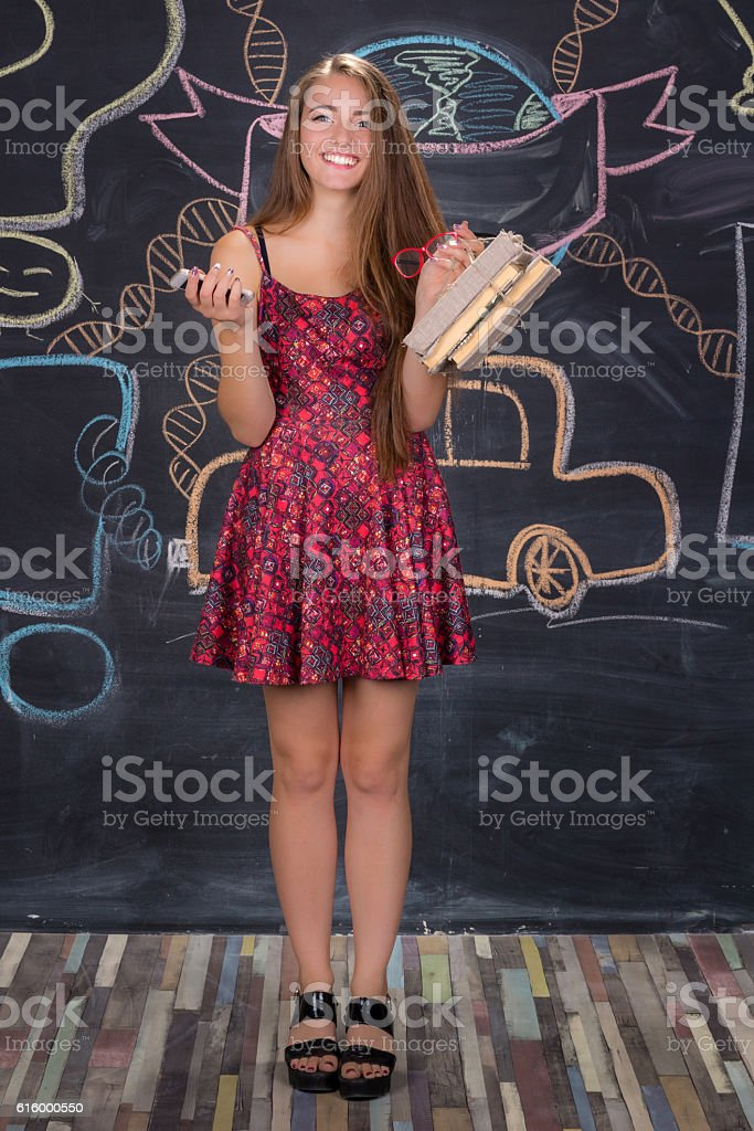 Student girl with books stands in front of class blackboard stock photo