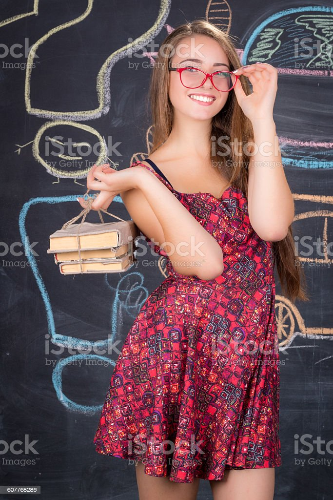 Student girl with pack of books poses near blackboard stock photo