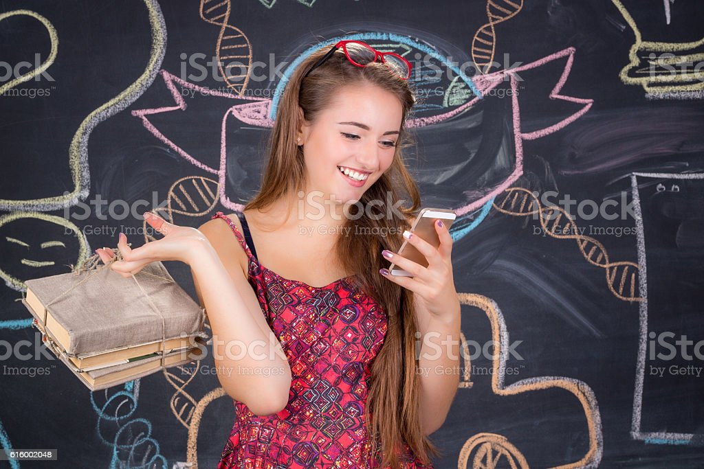 Student girl with pack of books poses near classroom blackboard stock photo
