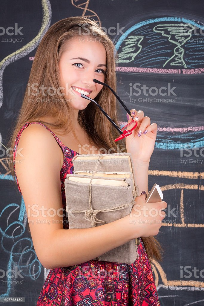 Student girl with pack of books stands near class blackboard stock photo