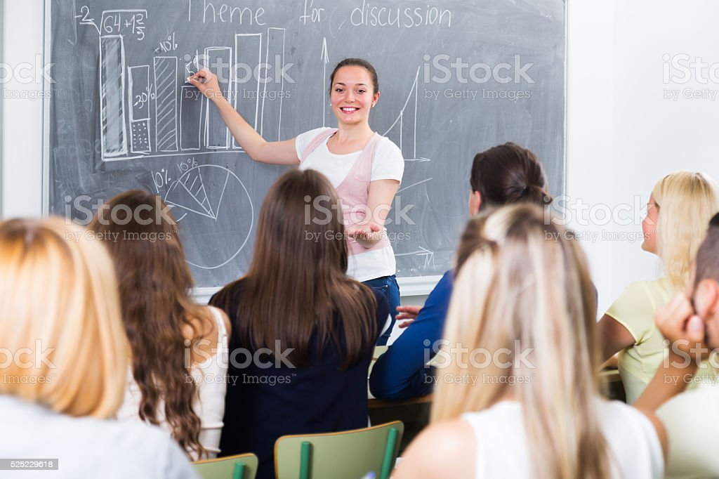 Student gives answer near blackboard stock photo