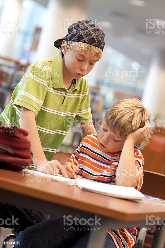 Student helping another doing homework stock photo