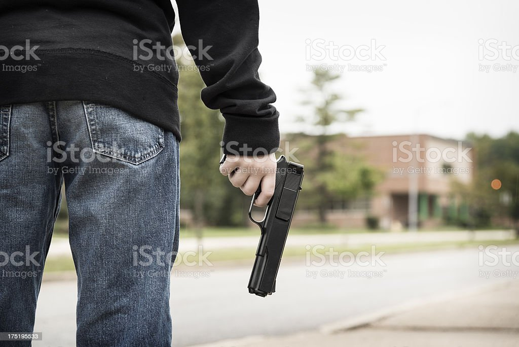 Student Holding a Gun Outside of School stock photo