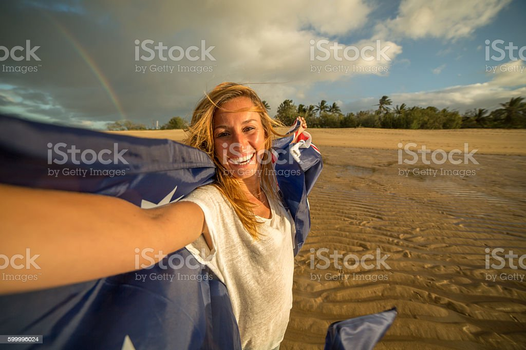 Student holding Australian flag on beach stock photo