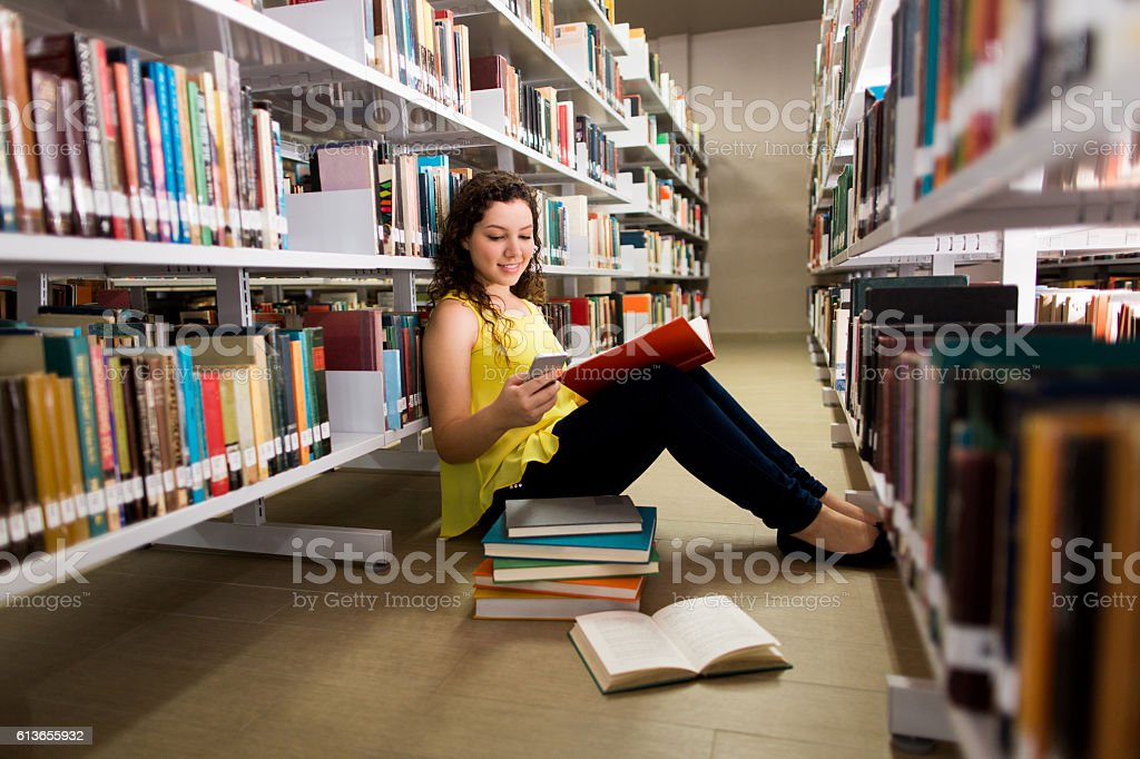 Student holding book and being distracted with mobile phone stock photo