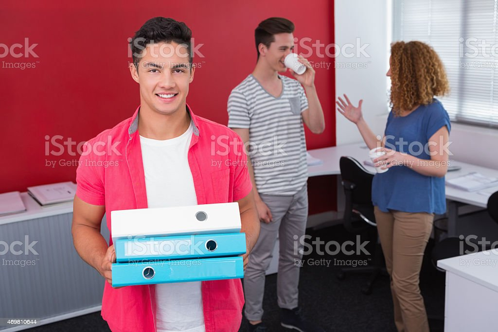 Student holding pile of ring binder near classmates with coffee stock photo