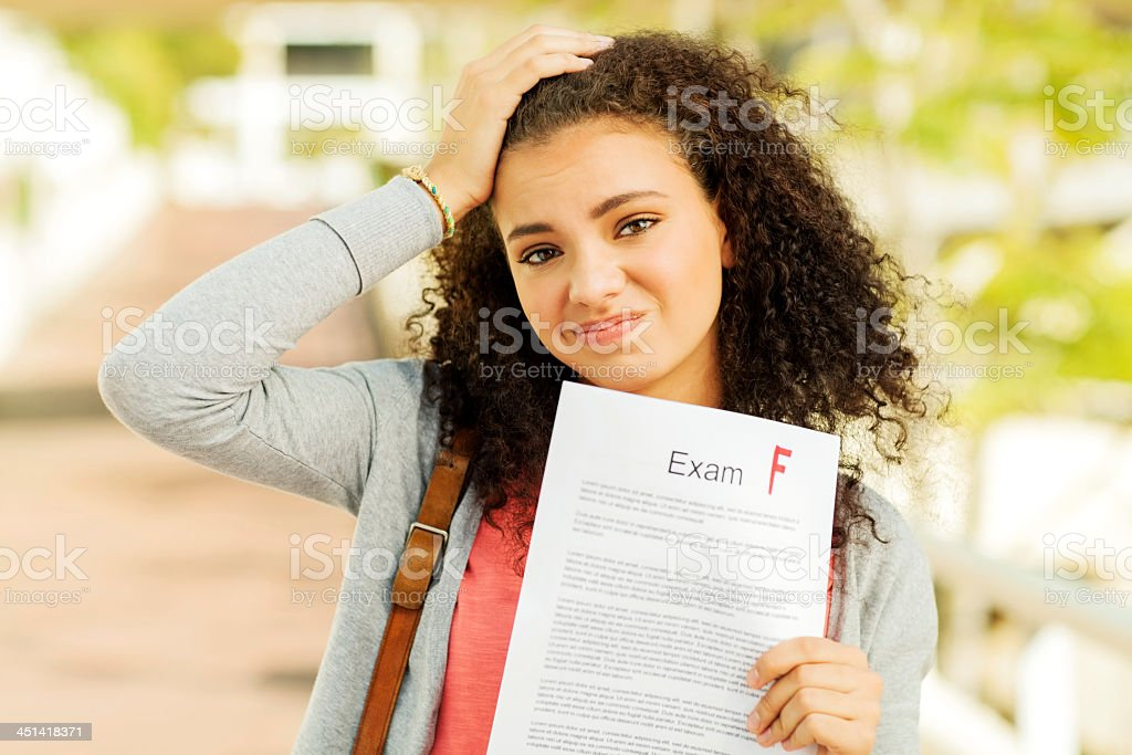 Student Holding Test Result With F Grade On University Sidewalk stock photo