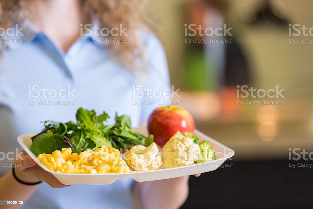 Student holding tray of healthy food in school cafeteria lunchroom stock photo