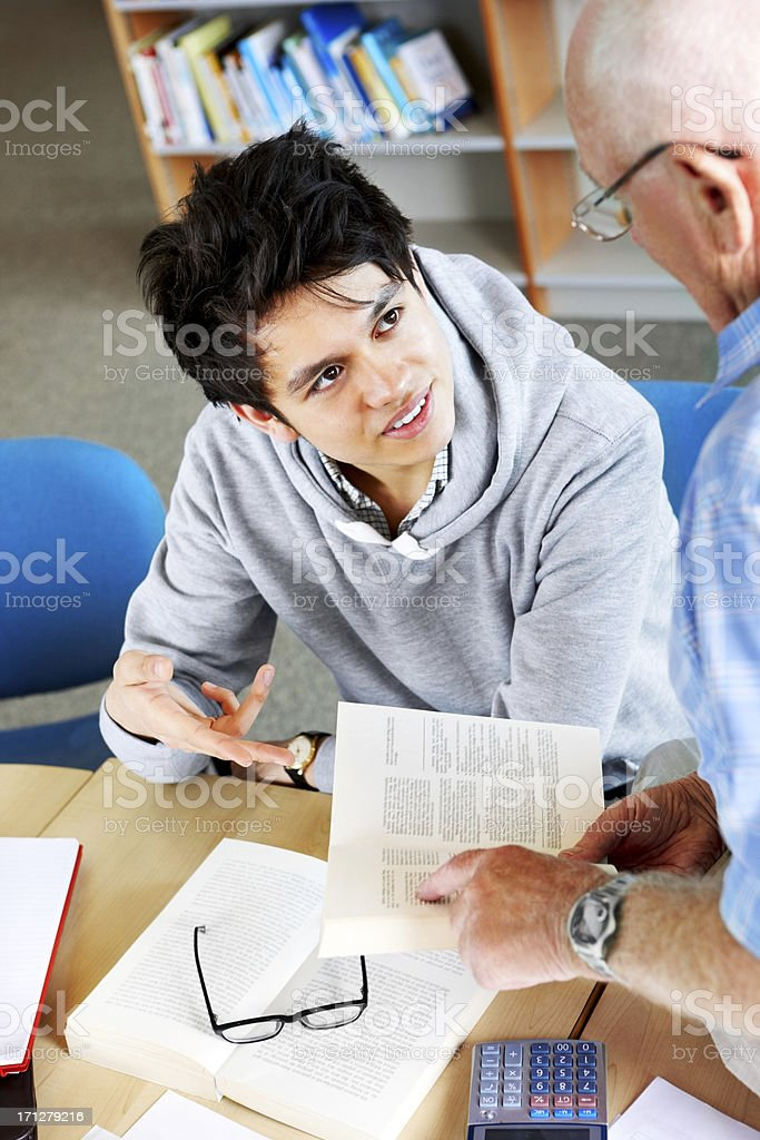 Student in class with teacher helping him royalty-free stock photo