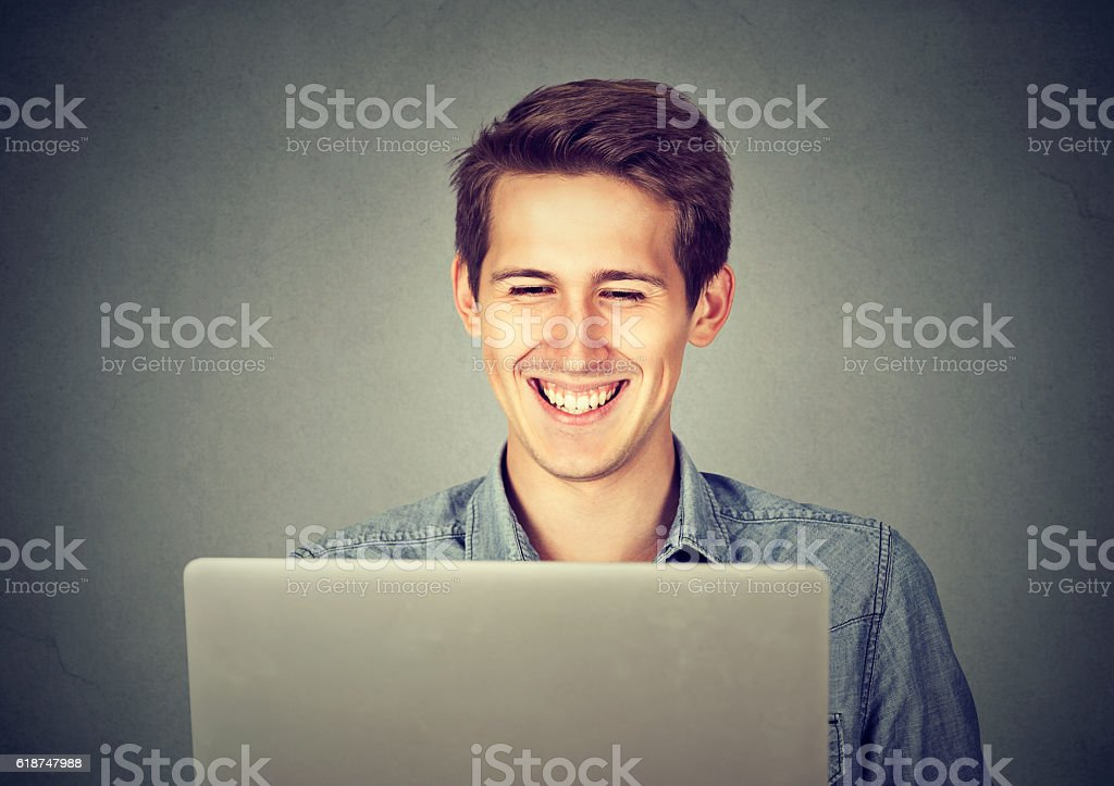 student in jeans shirt using a laptop smiling stock photo
