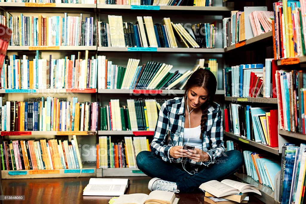 Student in the library listening music stock photo