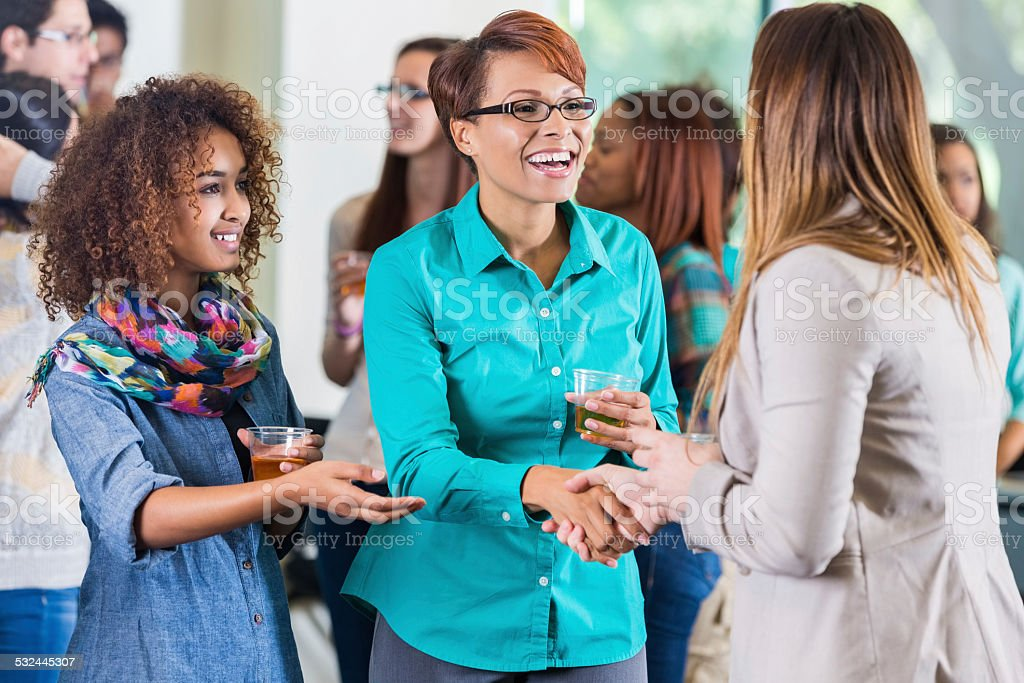 Student introducing parent to teacher during meet and greet party stock photo
