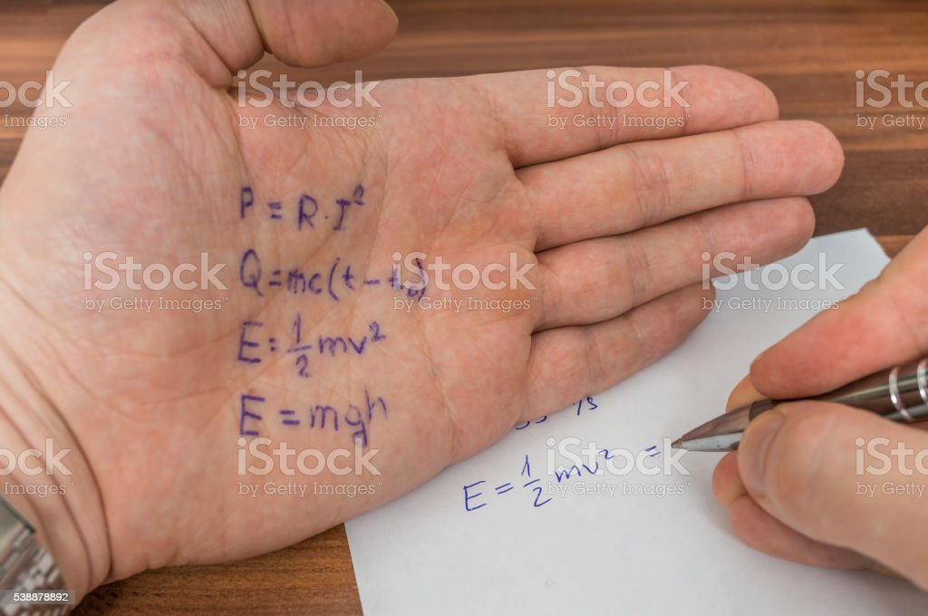 Student is cheating during exam with cheat sheet with formula. stock photo