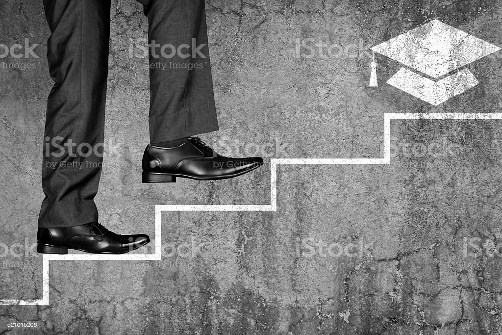 Student is climbing up to get university degree stock photo