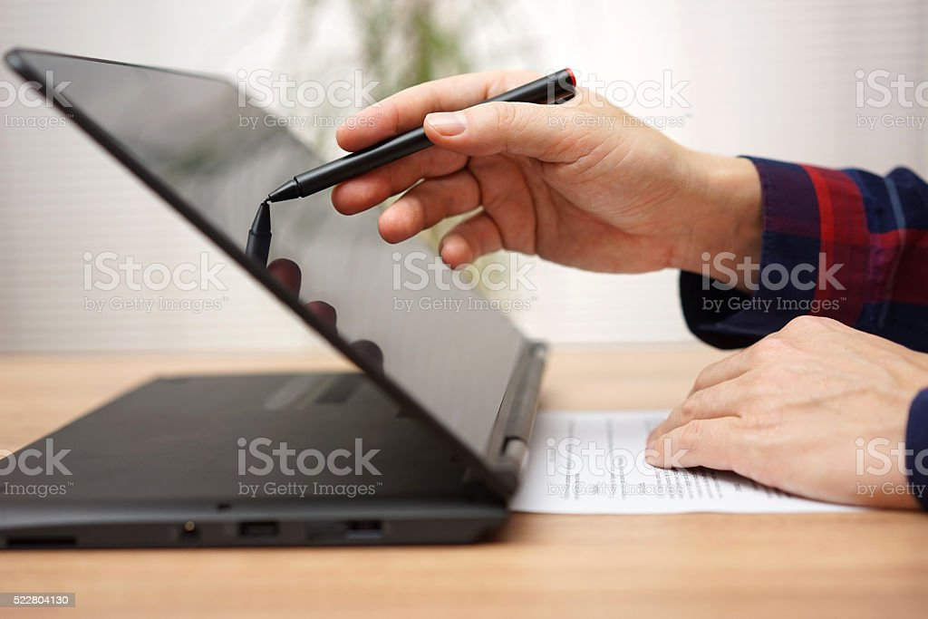 Student is taking on line course on touchscreen laptop computer stock photo