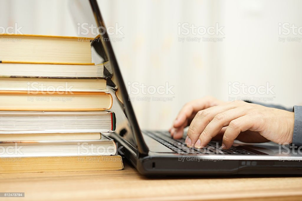 Student is using laptop and books to prepare for exam