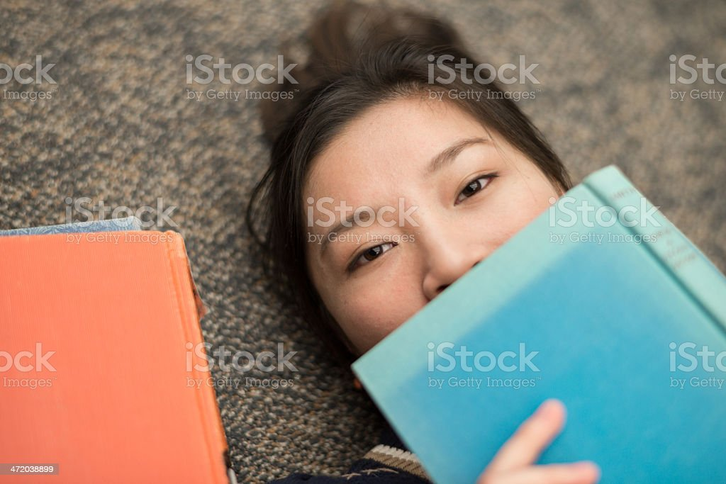Student laying on carpet with books royalty-free stock photo