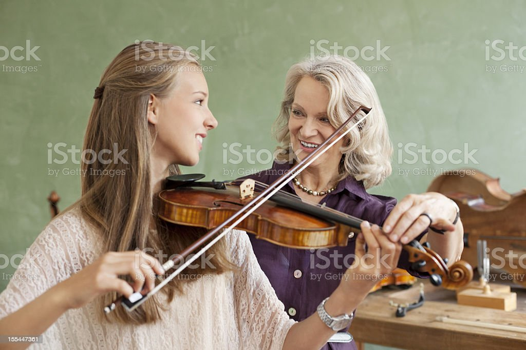 Student learning how to play violin stock photo