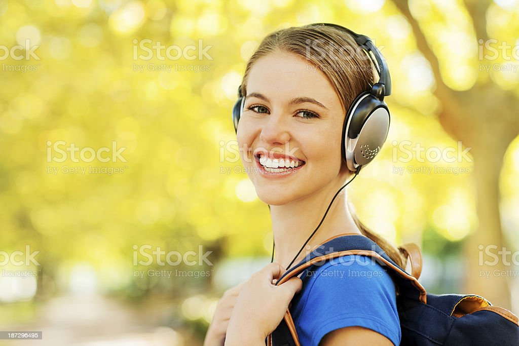 Student Listening To Music On Headphones At Campus royalty-free stock photo