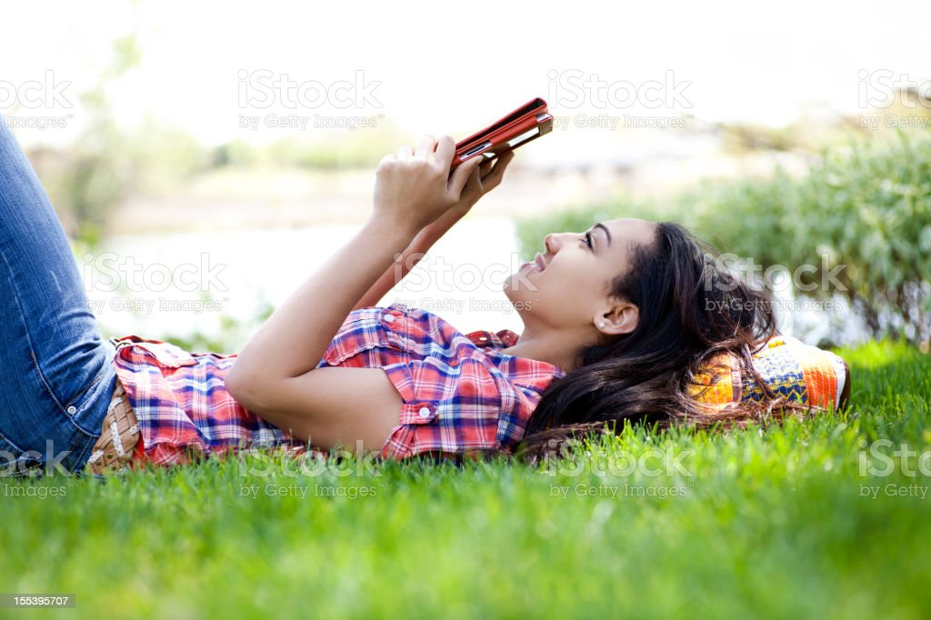 A student lying in the grass looking at a digital tablet  royalty-free stock photo