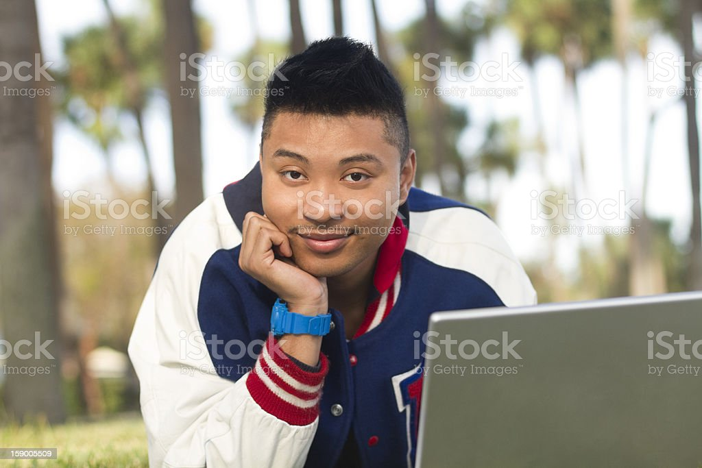 Student lying on grass with laptop stock photo