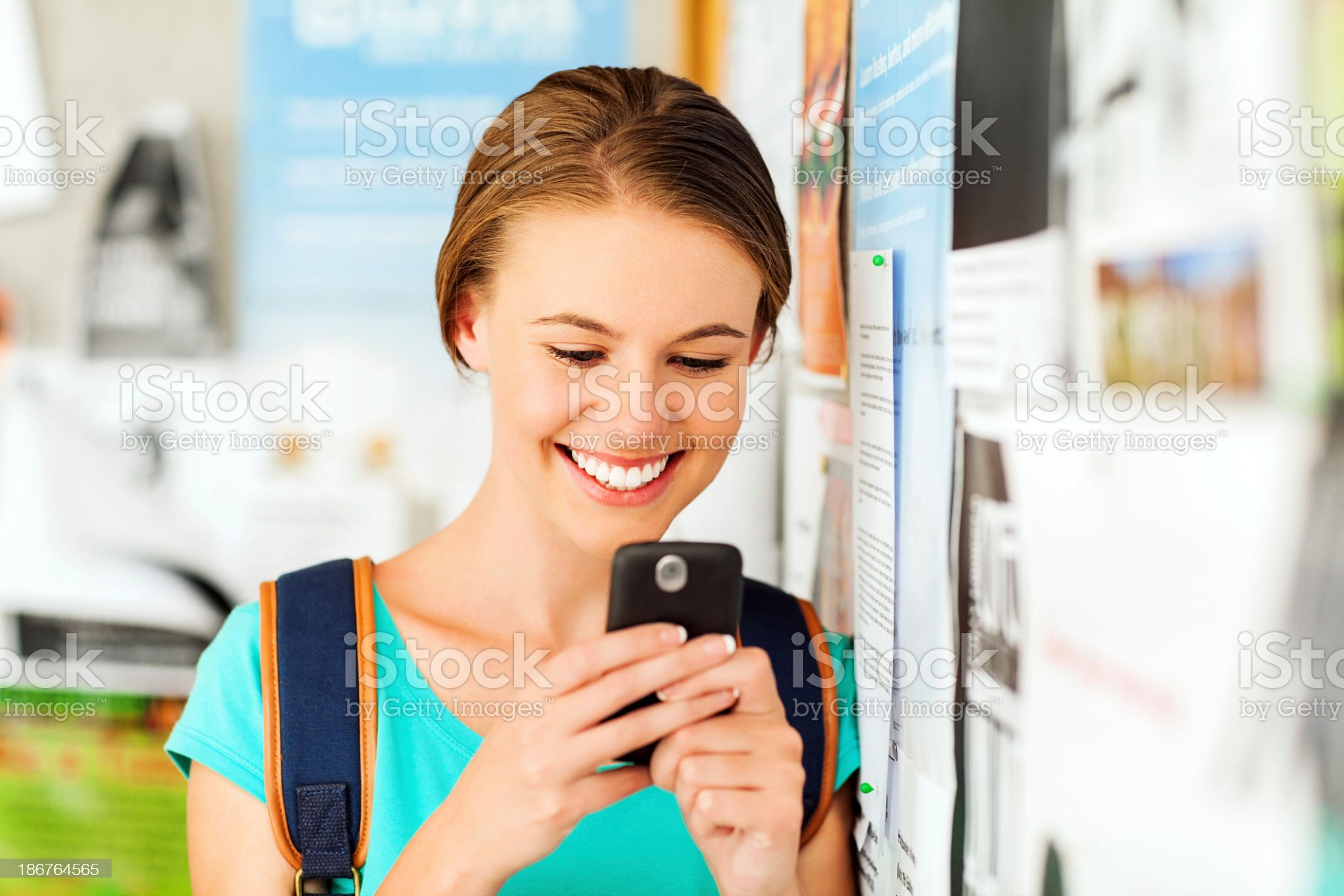 Student Messaging Through Smart Phone While Leaning On Bulletin royalty-free stock photo