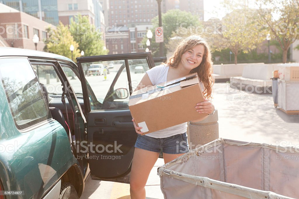 Student Moving Box from Car to Dormitory on College Campus stock photo