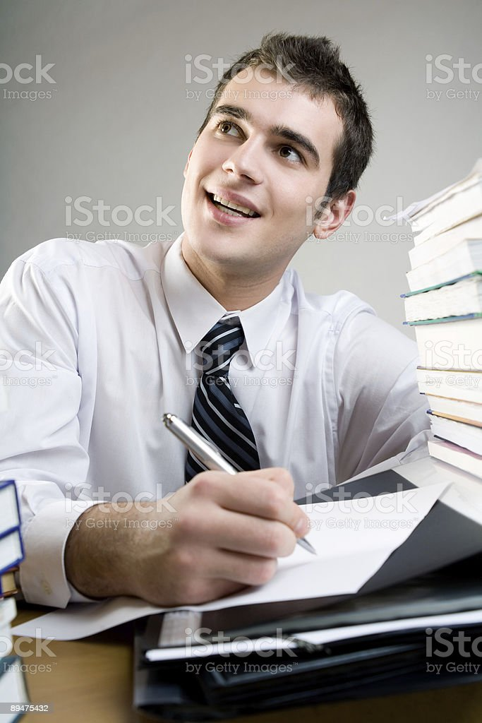 Student or businessman writing something on blank paper, smiling royalty-free stock photo