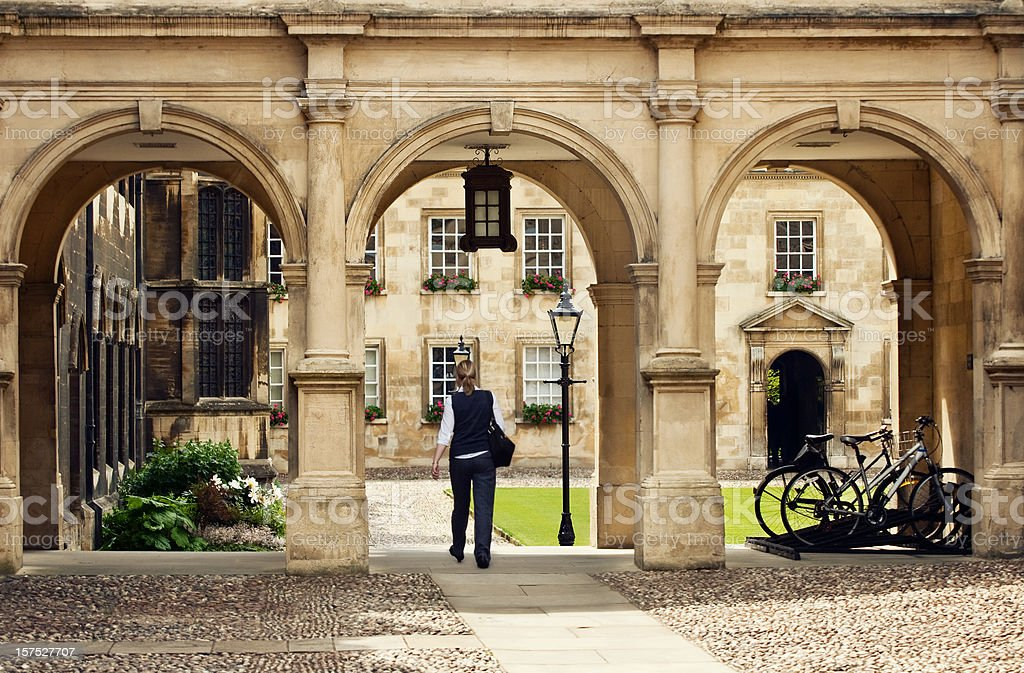 Student passing through a college campus in Cambridge Universitiy, UK stock photo