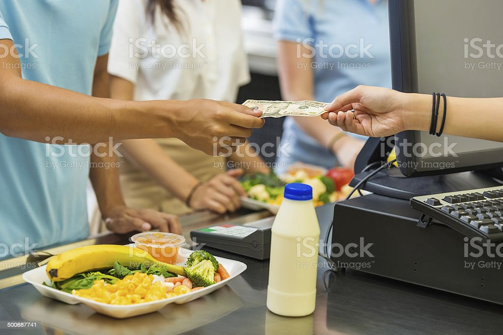 Student paying for school lunch with cash in cafeteria stock photo