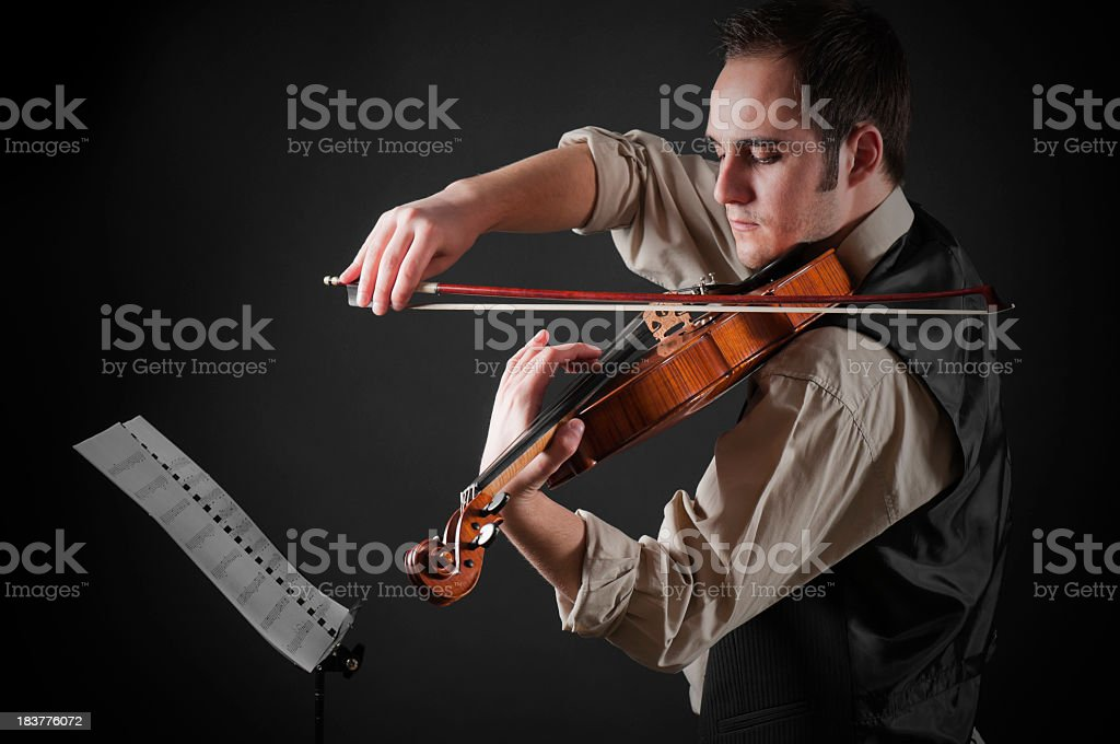 Student practicing violin, black background royalty-free stock photo
