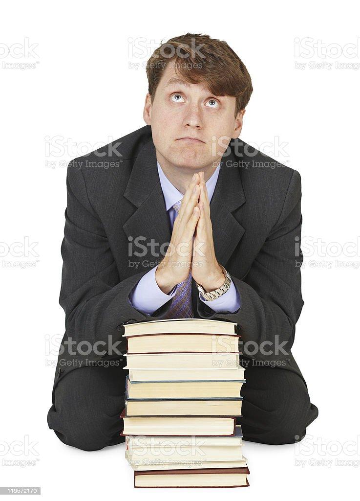 Student prays before examination on pile of textbooks royalty-free stock photo