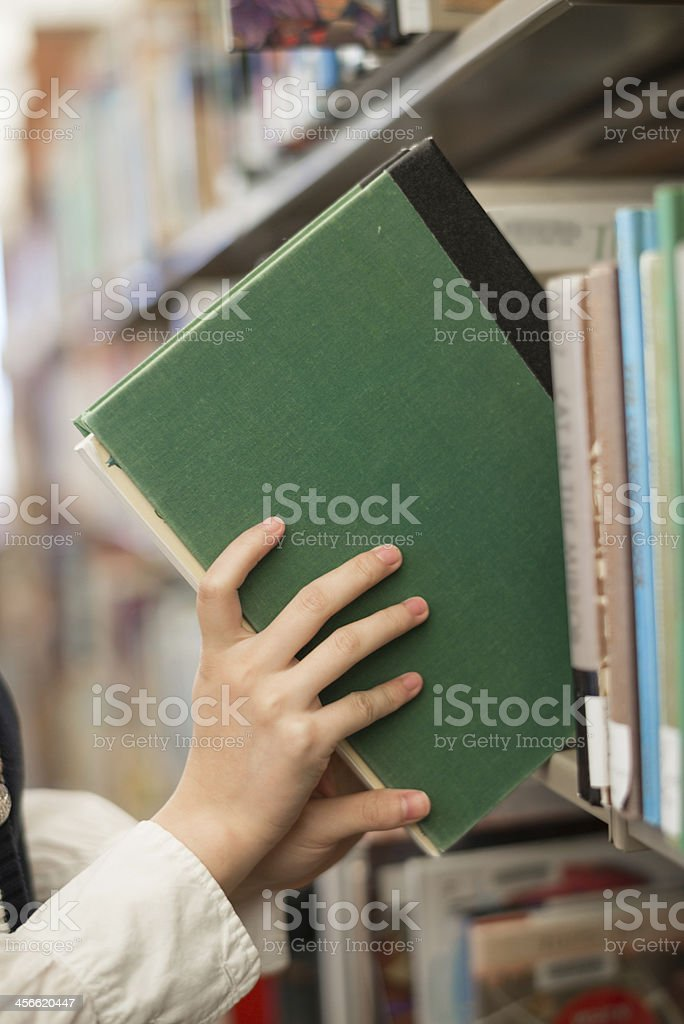 Student putting book back onto a bookshelf stock photo