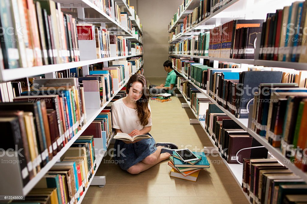Student reading a book on the floor of a library stock photo