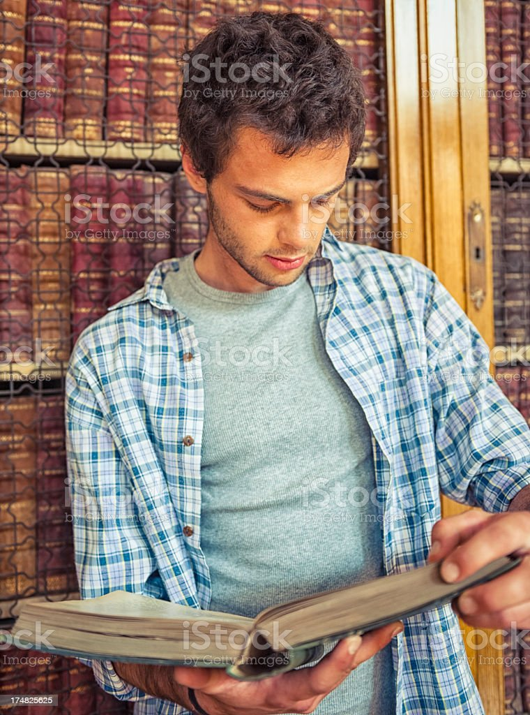 Student reading a book on the library royalty-free stock photo