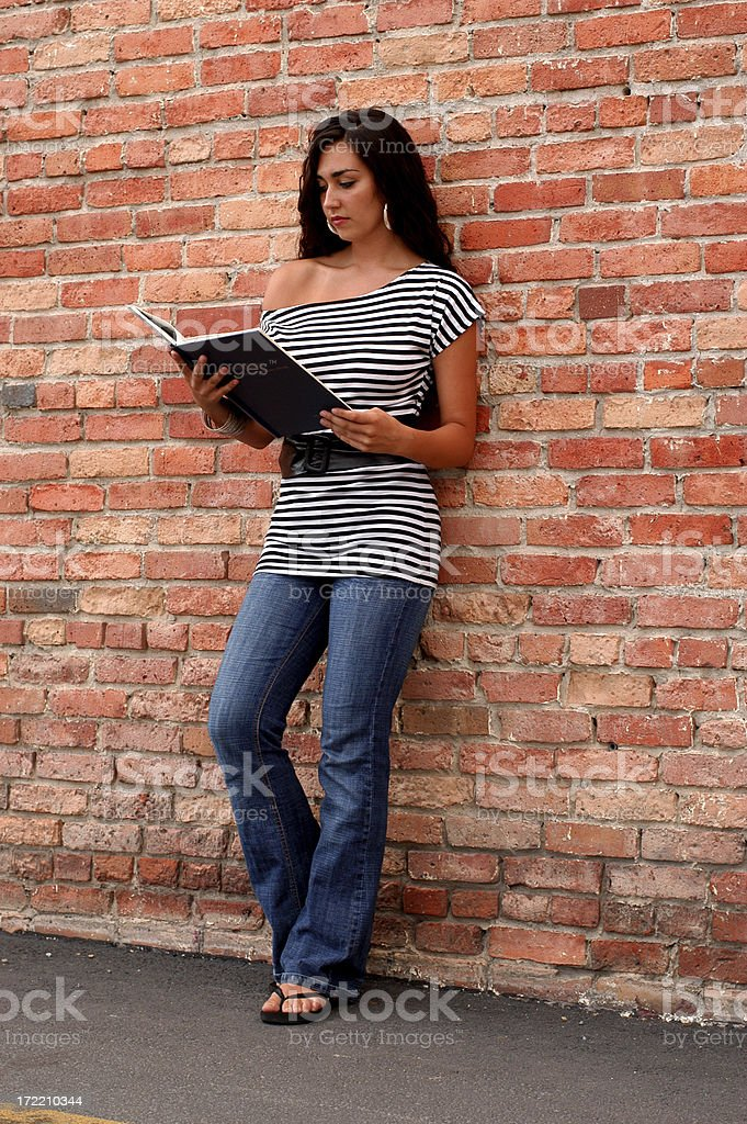 Student reading by a brick wall royalty-free stock photo