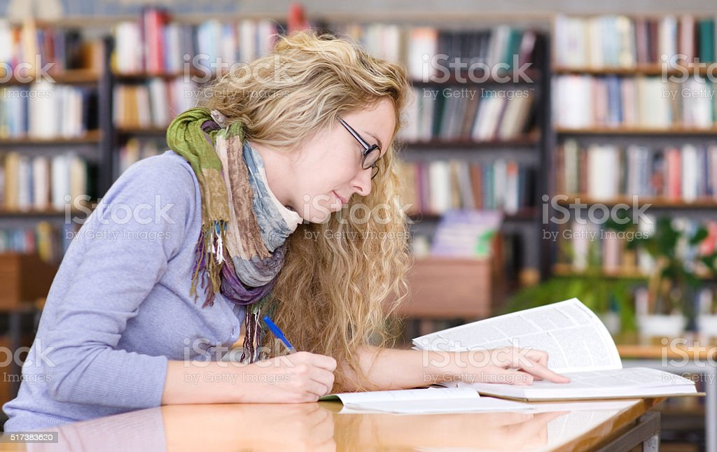 student reads the book in library stock photo