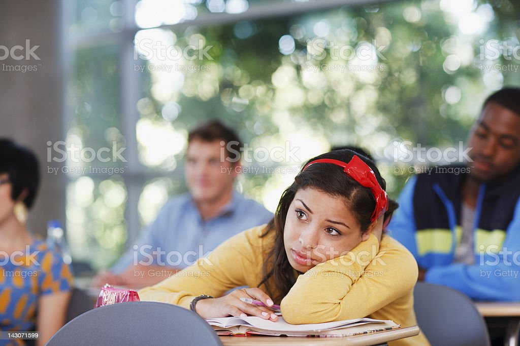 Student resting head on desk in classroom royalty-free stock photo