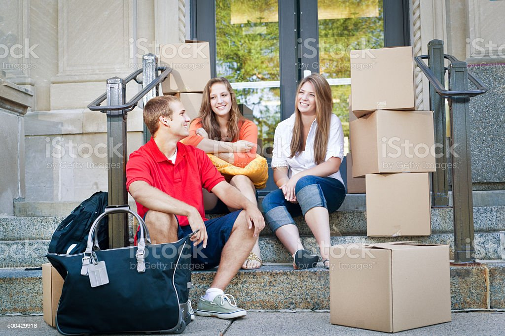 Student Roommates Moving into College Dormitory Apartment on University Campus stock photo