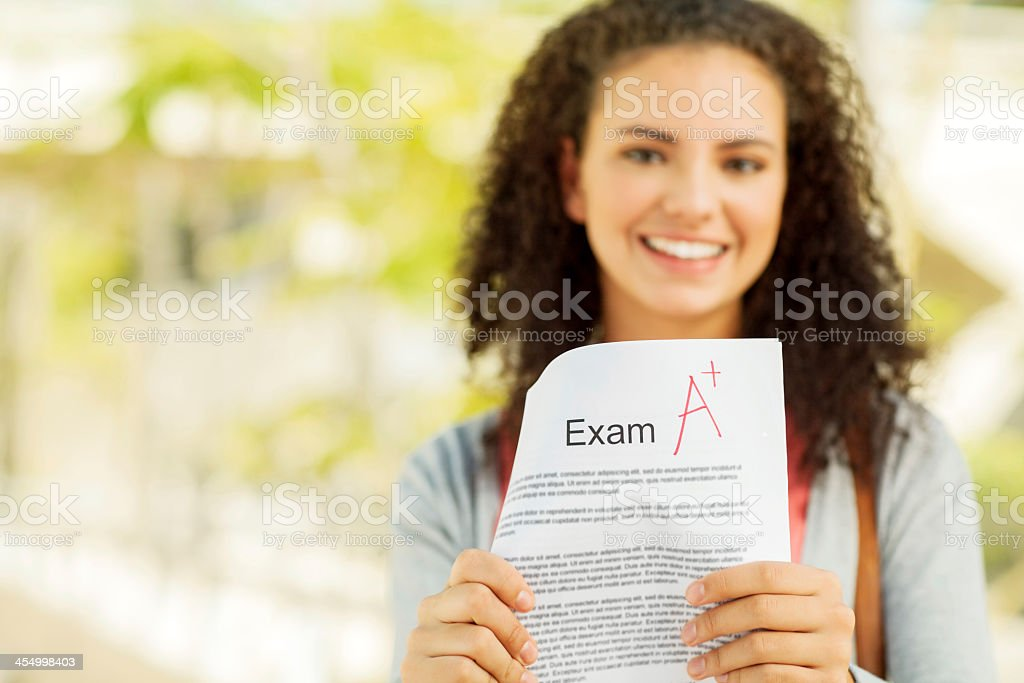Student Showing Exam Result With A+ Grade On Campus stock photo