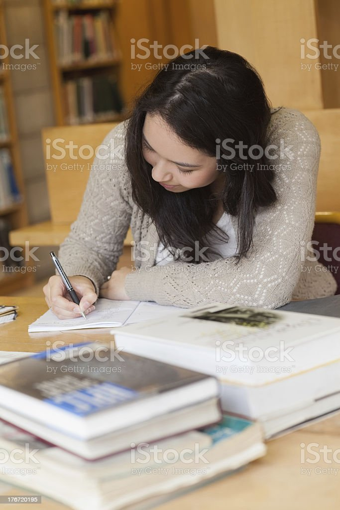 Student sitting in a library and writing royalty-free stock photo