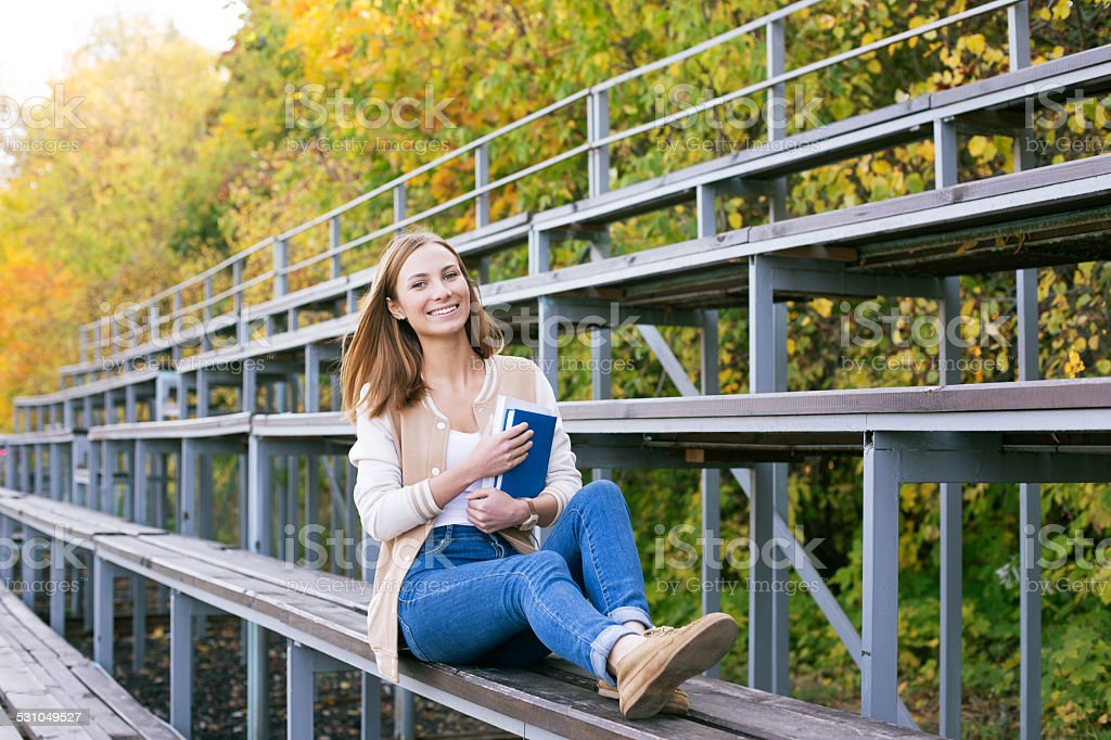 Student sitting on sport tribune with book stock photo