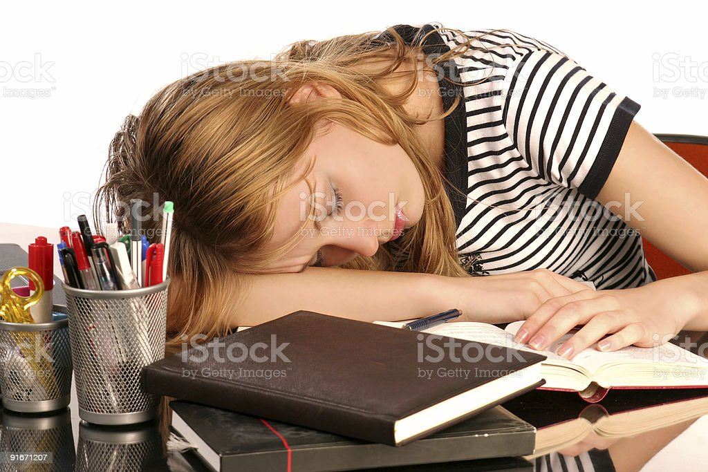 Student sleeping on a desk with open books and pens royalty-free stock photo