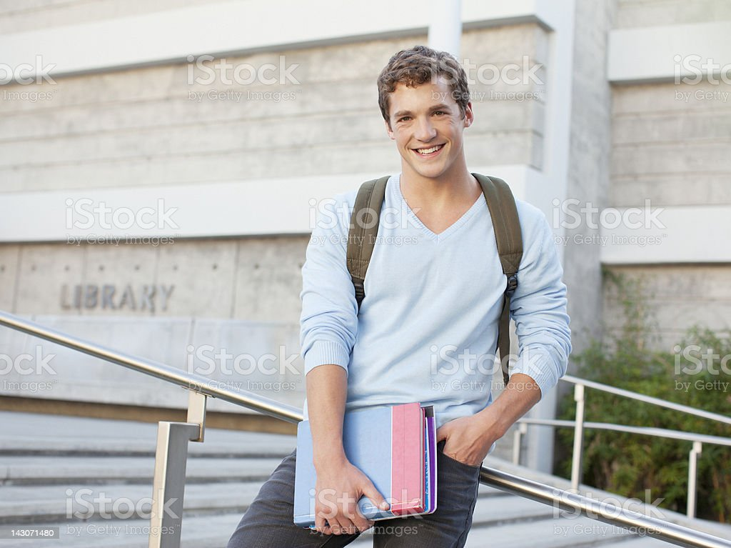 Student standing on steps outdoors stock photo