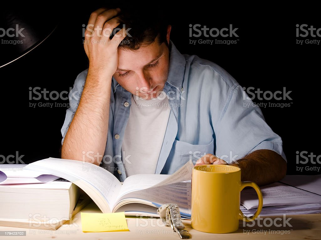 Student studying at night with a desk lamp on stock photo