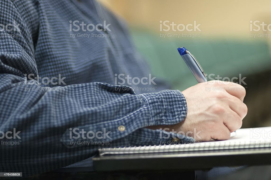Student Taking Notes in Lecture Hall royalty-free stock photo